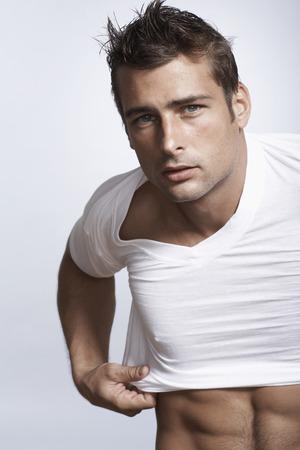 hombre caucasico: Caucasian man putting on t-shirt
