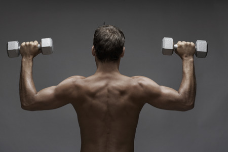 grabbing back: Back view of a man lifting dumbbells