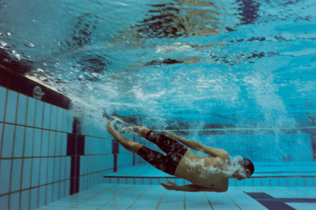 into: Man diving into swimming pool Stock Photo