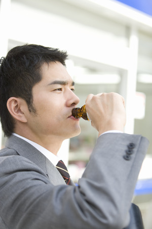 energized: Young man drinking from a bottle