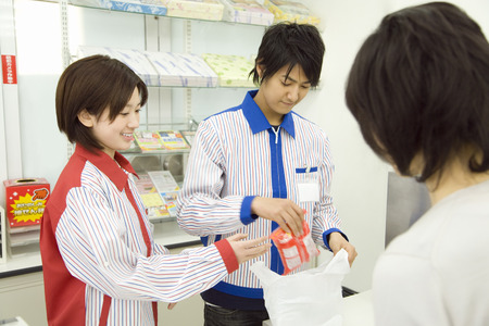 purchased: Cashiers putting purchased items into a bag