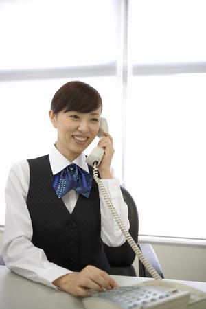 answering phone: Recepcionista asi�tica tel�fono contestador Foto de archivo