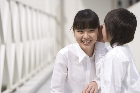 girl squatting: Asian boy whispering to mother Stock Photo