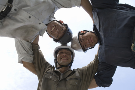 huddling: Construction workers huddling together and smiling Stock Photo