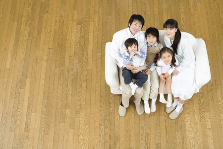 kanapa: Asian family sitting on couch