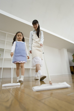 Asian mother and daughter cleaning floor together Stock Photo