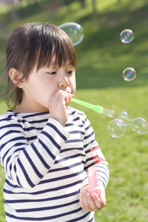 blowing bubbles: Asian girl blowing bubbles Stock Photo