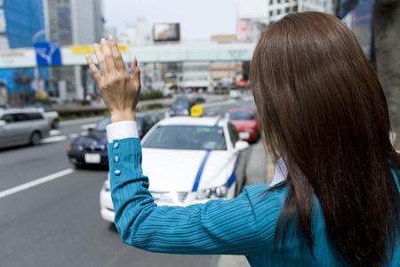 hailing: Asian woman hailing a taxi Stock Photo
