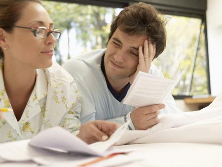 echtgenoot: Man en vrouw het controleren van facturen Stockfoto