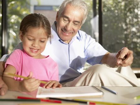 guiding: Grandfather guiding his granddaughter with her homework