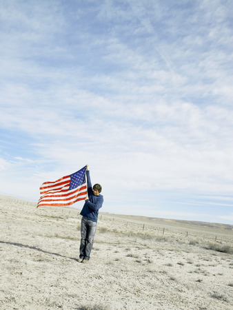young man: Young man in desert holding American flag