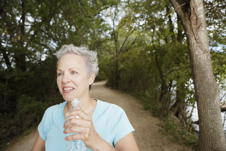 bottled water: Senior woman with a bottled water in the park Stock Photo