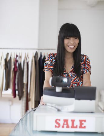 sales clerk: Sales clerk smiling in clothing shop Stock Photo