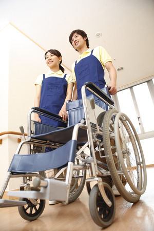 japanese ethnicity: Man and woman holding a wheelchair Stock Photo
