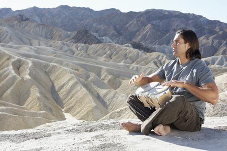 bongos: Young man playing bongos in the desert Stock Photo