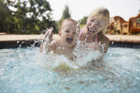 peo: Mother and baby boy splashing in the swimming pool