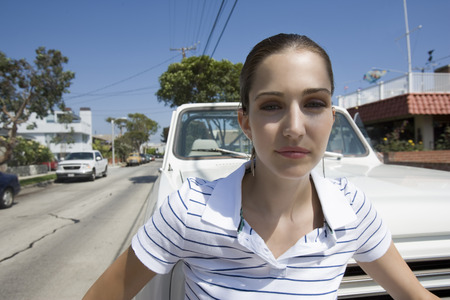 leaning on the truck: Caucasian woman standing in front of a pick up truck Stock Photo