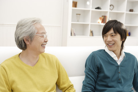 japanese ethnicity: Father and son talking on sofa