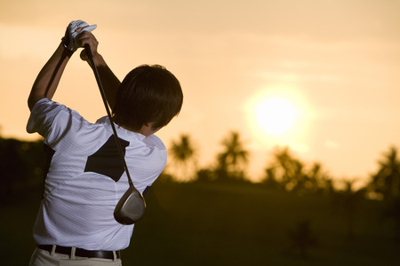 japanese ethnicity: Male golfer playing at dusk time