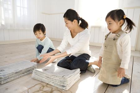 bundling: Mother and children bundling newspaper