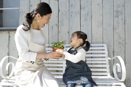 japanese ethnicity: Mother and daughter laughing while holding potted plant