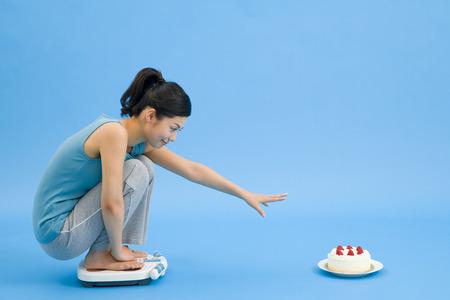 diets: Woman on a weight scale trying to get the cake Stock Photo