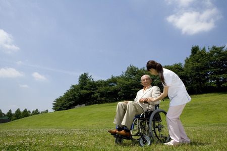 nursing staff: Senior man sitting in wheelchair talking to nursing staff