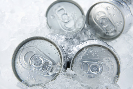 crushed cans: Canned beer among ice cubes Stock Photo