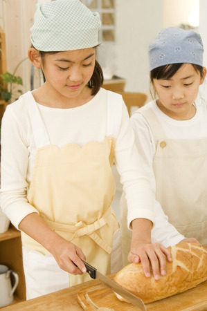 japanese ethnicity: Girl slicing bun in the kitchen