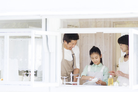 wash dishes: Girl helping parents to wash dishes in the kitchen