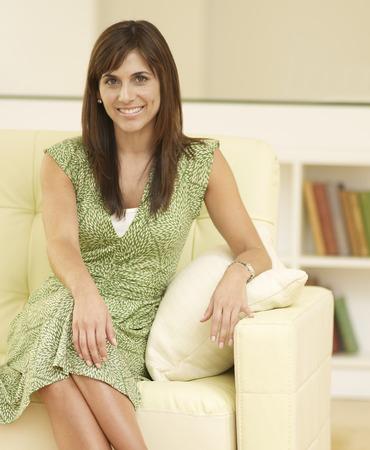 kanapa: Portrait of woman sitting on couch Zdjęcie Seryjne