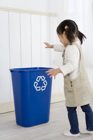 papelera de reciclaje: Muchacha que lanza cosas en la papelera de reciclaje