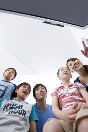 people watching tv: Una familia de cinco personas viendo la televisi�n juntos