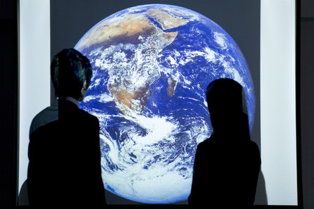 two people only: Man and woman looking at globe on projection screen Stock Photo
