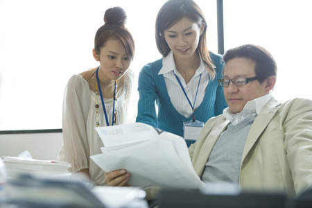 three people only: Women discussing report with their boss Stock Photo