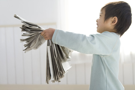 one person only: Boy holding a stack of old newspapers