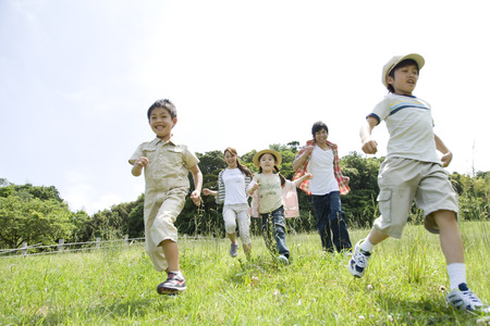 A happy family of five people running on grassland