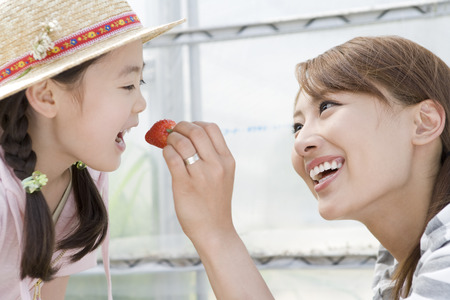 japanese ethnicity: Mother feeding daughter strawberry