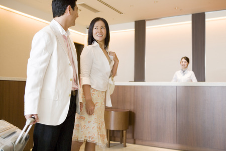 baggage: Asian couple at hotel reception