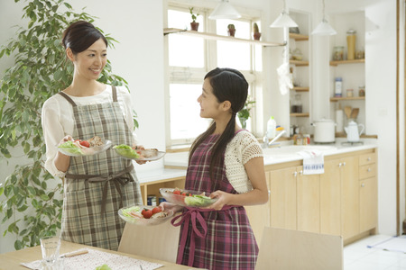 Mother and daughter serving food Stock Photo