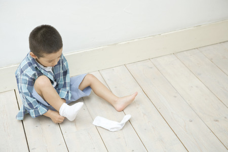 independently: Boy putting on socks