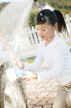 body wash: Little girl doing Car Wash Stock Photo