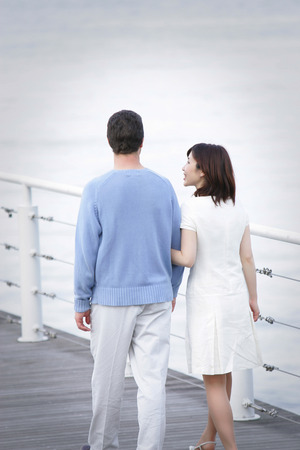 fold ones arms: Couple walking together Stock Photo
