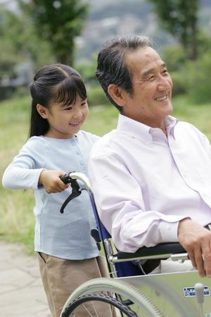 ni�o empujando: Ni�o empujando su abuelo en silla de ruedas Foto de archivo