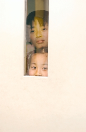 other side of: Two Girls Peaking from Other Side of Door