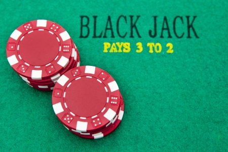 black jack table with red casino chips photo