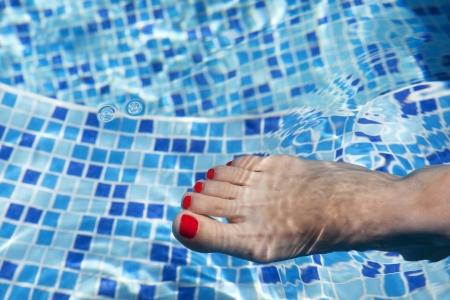 long toes: Sexy women legs splashing in tropical swimming pool