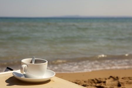 Cup of coffee at the beach photo