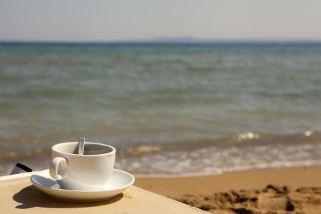 disfrutar: Taza de caf� en la playa Foto de archivo