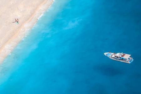 zakynthos: Boat on the ionic sea, a romantic couple at the beach Stock Photo
